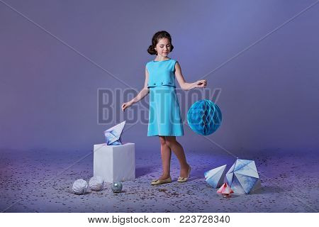 Pretty girl in an elegant blue dress for teenage girls with a make-up. Origami and minimalism. Fashion kid. Designer collection. Charming teenager girl in studio holds an origami figure. Free space for text and advertising.