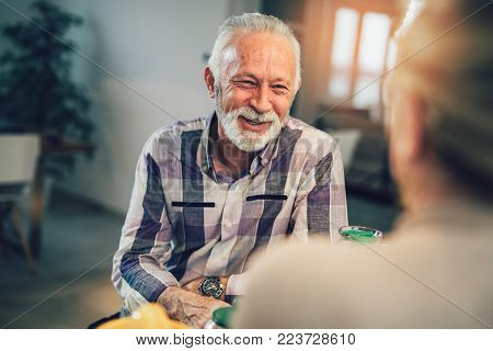 Portrait of happy senior man sitting at breakfast table, smiling at camera, sitting with wife.