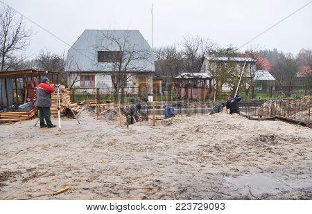 KYIV, UKRAINE - January 29, 2018: Building contractors pouring a concrete slab formwork along the foundation.