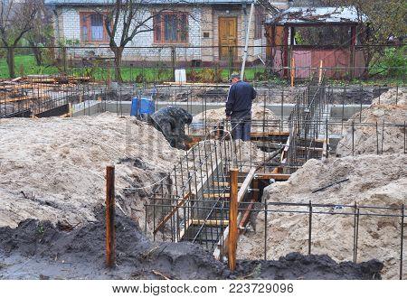 Kyiv, Ukraine - February, 12, 2018:  Builders Pouring A Concrete Slab Formwork Along The Foundation.