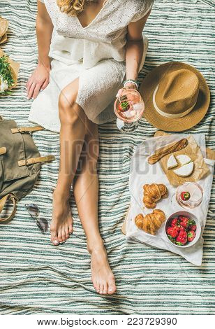 French style romantic picnic setting. Woman in dress with glass of wine, strawberries, croissants, brie cheese, sunglasses, straw hat, peony flowers on blanket, top view. Outdoor gathering concept