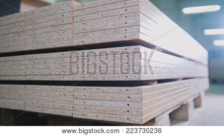 Stack of wood particleboard panels on the warehouse or factory, industrial concept
