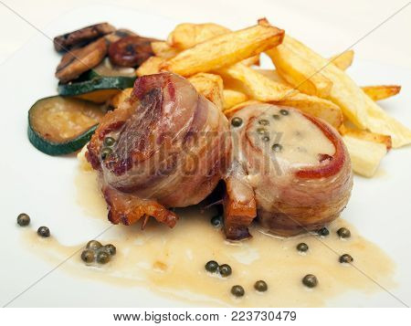 Closeup view of tasty bacon wrapped steaks with green pepper sauce, french fry potatoes and roasted vegetables.