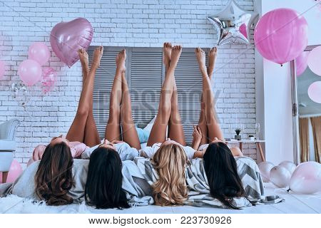 Perfect view. Playful young women keeping feet up while lying on the bed