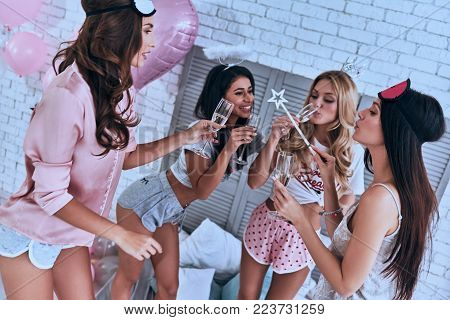 Private party. Four attractive young smiling women in pajamas toasting each other while having a slumber party in the bedroom