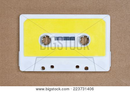 Retro white audio tape with yellow label on brown background