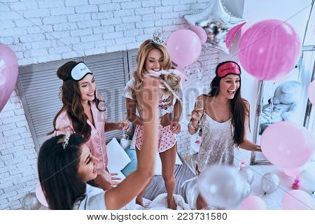 Enjoying carefree time. Top view of four attractive young smiling women in pajamas drinking champagne while having a slumber party in the bedroom