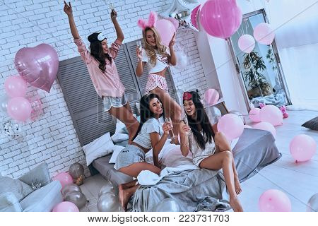 Party is impossible without champagne! Top view of four playful young smiling women in pajamas bonding together while having a slumber party in the bedroom with balloons all over the place