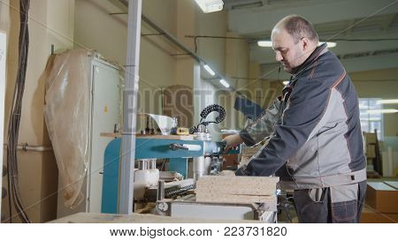 Carpenter cut a wooden workpiece on a furniture factory, woodworking