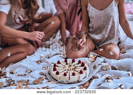Close up of four young women in pajamas getting ready to eat cake while having a slumber party