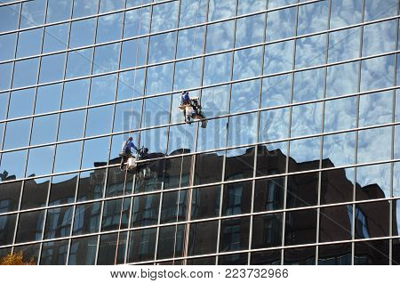 On a glass wall. Washing of windows in the multi-story building.