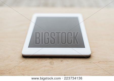 one turned off tablet on wooden table