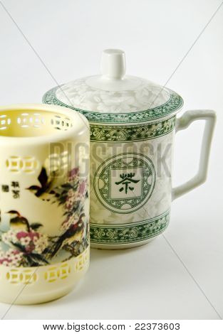 Chinese ornate mug and a vase over white background. Shallow depth of field.
