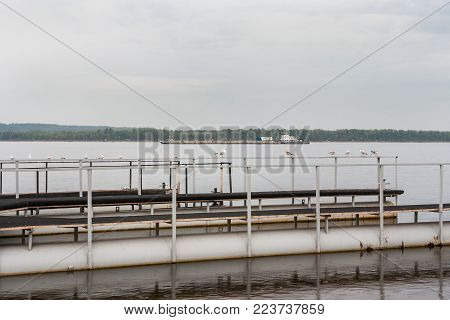 Metal platform for mooring of boats with seagulls on handrail in the foreground and large barge in the background on the Volga river.