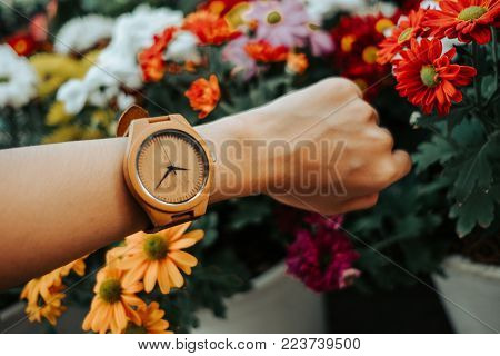 Hand Business Woman Wearing Wooden Watch With Copy Space And Beautiful Flowers Background. Image For