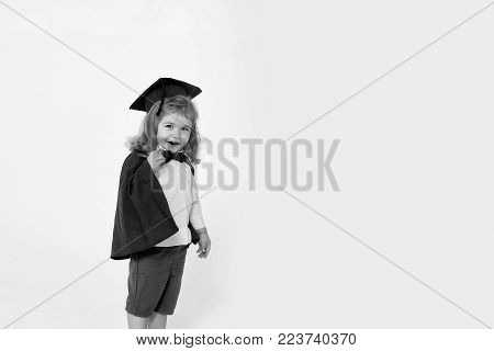 Small Boy Child Blond With Smiling Sly Face In Blue Shirt Black Graduation Squared Cap Gown And Bow-