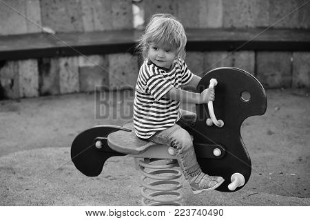 Cute Happy Baby Boy With Blond Hair In Blue Tshirt And Jeans Riding Red Spring Rider Or Rocker On Su