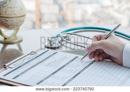 Physician Doctor Writing On Medical Health Care Record, Patients Discharge, Or Prescription Form Pap