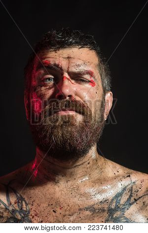 Man With Beard, Mustache On Brutal Bloody Face. Bearded Hipster With Tattoo On Chest On Black Backgr