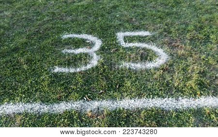 Starting block for a high school cross country running race is painted on to the grass and is box number 35.