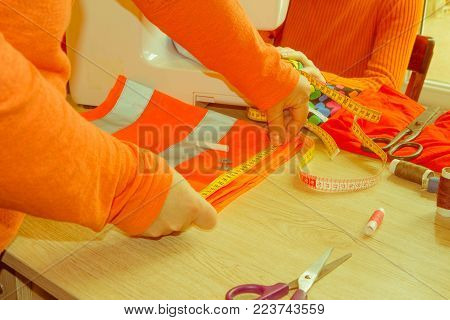 pattern, scissors, tape measure, and a sewing machine. Workplace of seamstress. Dressmaker cuts dress detail on the sketch lines. woman seamstress sews on sewing machine