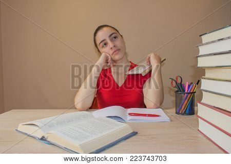 Young Girl studying on desk at home. Thoughts, education, creativity concept