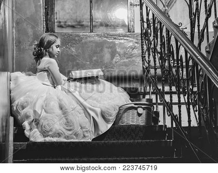 small girl kid with long blonde hair and pretty face in prom princess white dress with basket sitting near building glass big window on stairs reading book