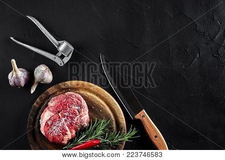 Fresh raw meat. Beef. Piece of beef steak tenderloin, with knife for cutting and chopping meat, spices were cooking - rosemary, pepper, salt, garlic. On old wooden board on stone black table. Top view copy space