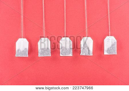 top view of five unused tea bags isolated on red
