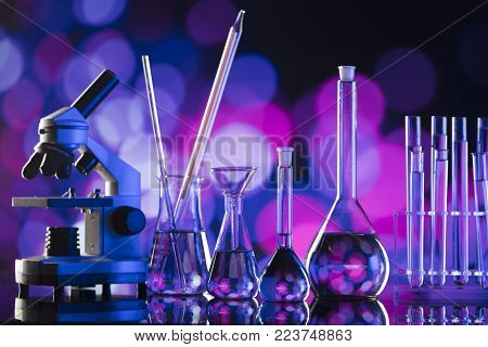Science experiment concept background. Laboratory beakers, microscope, pipette.  Bokeh background.