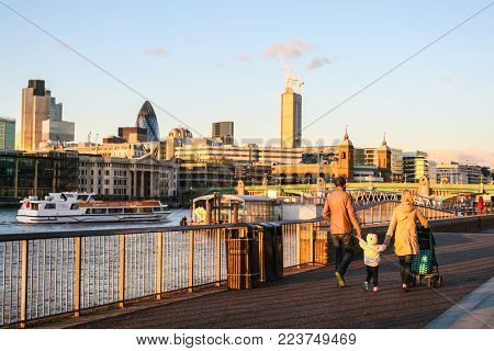 LONDON, ENGLAND -  MAY 11, 2012 : People are walking at a riverfront near Millennium Bridge which crossing the River Thames during the evening