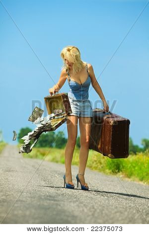 Shocked woman holding  opening suitcases with cash on countryside road