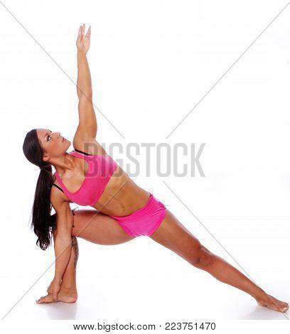 Portrait of joga trainer in pink sportwear posing in studio