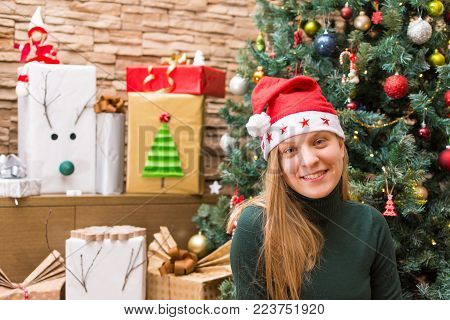Smiling Teenage Girl Wearing Santa Hat with Gifts and Christmas Tree