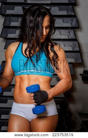 Athletic brunette fitness girl in sexy sportswear doing exercises with dumbells in a gym.