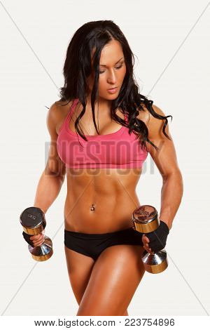 Strong athletic fitness woman in colorful sportswear holds pait of dumbells. Isolated on white background.