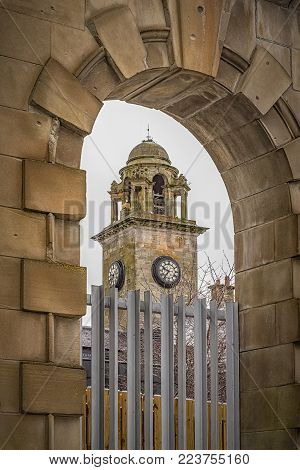 A view of the town hall clock tower in Clydebank through a nearby archway.