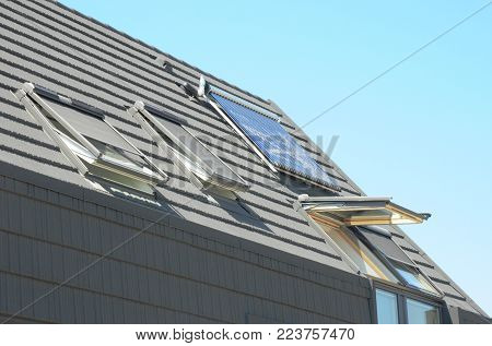 Modern House Roof with Solar Water Heater, Solar Panels and Skylights. Attic House with Solar Panels, Skylights and Dormer. Modern Home Roofing Construction.