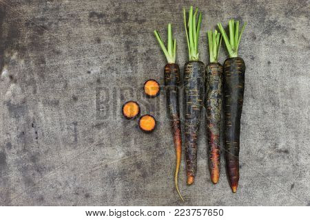 black carrots and some cut pieces on a grungy metal background