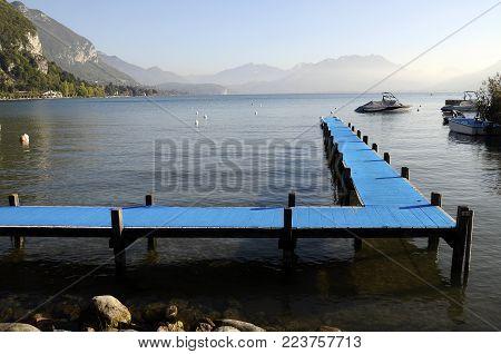 Wooden, pontoon, and, blue carpet landscape on Annecy lake, Savoy, France