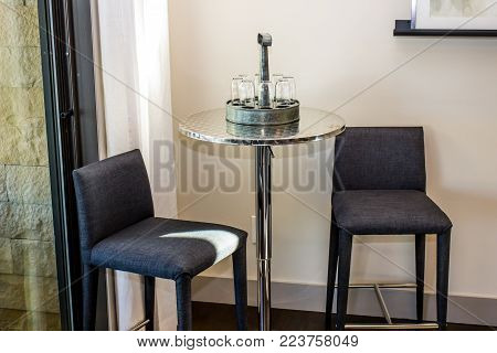 Two High Back Stools By Round Corner Table With Glasses