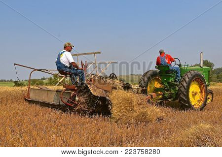 ROLLAG, MINNESOTA, Sept 2, 2017: Unidentified operators of a John Deere 60 tractor a grain binder are field demonstrating at the annual WCSTR farm show in Rollag held each Labor Day weekend where 1000's attend.