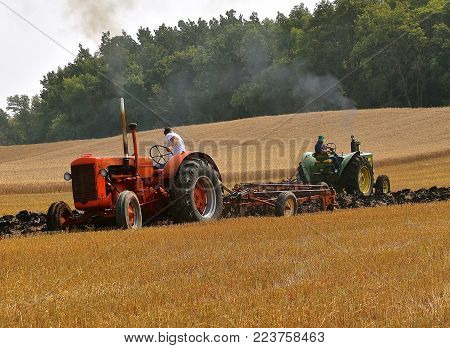 ROLLAG, MINNESOTA, Sept 2, 2017: Unidentified operators of a John Deere and Case Diesel 500 tractors are field demonstrating the process of plowing at the annual Rollag farm show held each 2nd weekend of September where 1000's attend.