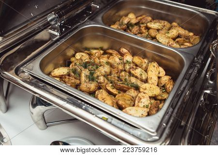 baked potatoes in a steel Chafing Dish. Restaurant.