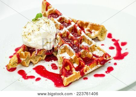 Belgium waffles with fruit sauce, ice cream with nut crumb and mint isolated on white background. Sprinkled with powdered sugar