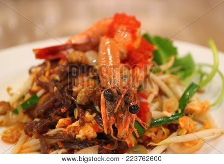 Thai Style Stir-fried Riceberry Noodles or Pad Thai Topped with Prawn Served on White Plate