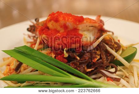 Pad Thai or Thai Style Stir-fried Riceberry Noodles Topped with Prawn Served on White Plate