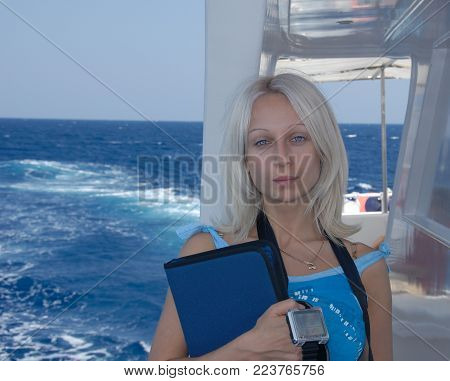 A portrait of a pretty young blonde girl or woman with blue eyes in a blue t-shirt in front of a blue sea. A girl is a diver, she stands on a diver's yacht and holds a logbook and a dive watch for scuba diving in her hands.