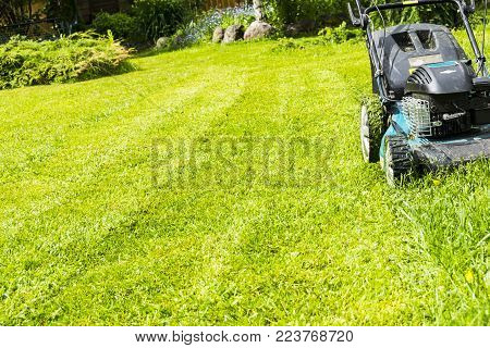 Mowing lawns, Lawn mower on green grass, mower grass equipment, mowing gardener care work tool, close up view, sunny day