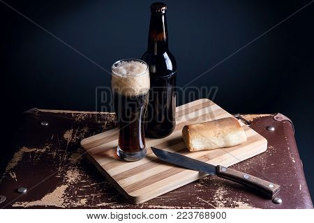 Glass And Bottle Of Dark Beer With Smoked Cheese On Cutting Board..